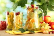 16106482-jar-and-glasses-with-citrus-fruits-and-raspberries-on-green-background